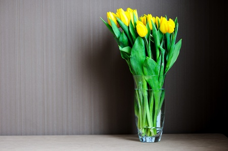 A bouquet of yellow tulips in a glass vase on a table against a dark background photo