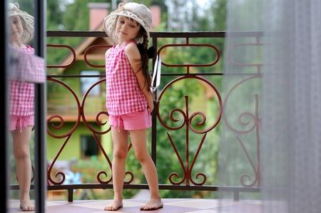 Fancy toddler girl in sunhat standing on balcony