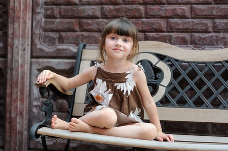 young girl feet: Portrait of cute smiling child sitting on bench - wall in background Stock Photo