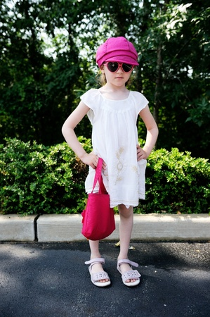 Beauty little girl in pink cap and heart-shaped sunglasses posing ourdoors photo