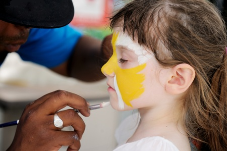 face paint: Cute little girl having her face painted on a hot summer day
