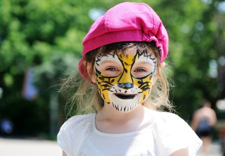 Cute little girl with face painted on a hot summer day photo