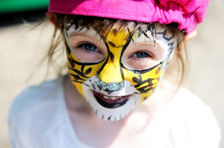 Cute little girl with face painted on a hot summer day