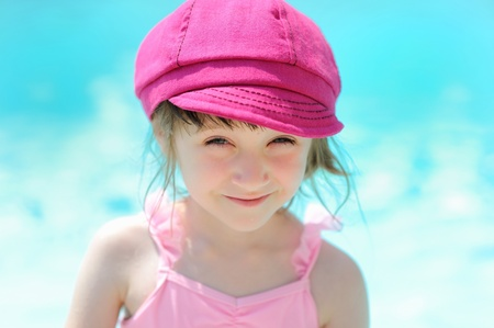 Cute little girl sitting by a swimming pool photo