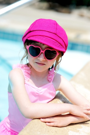 Cute little girl resting on the edge of swimming pool photo