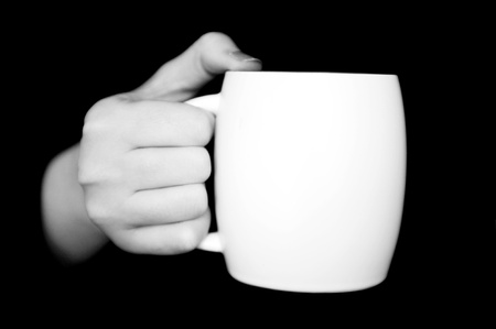 black coffee mug: Hand holding white cup isolated on black background Stock Photo