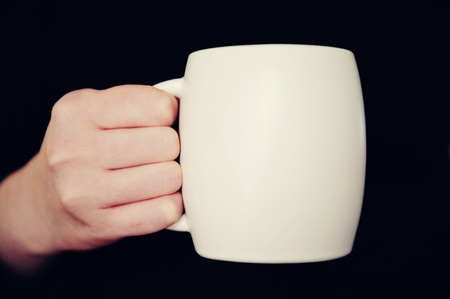 Hand holding white cup isolated on black background Stock Photo