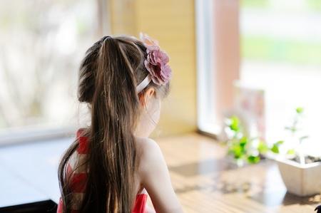 bambini pensierosi: Bambino bambina seduta a un tavolo rivolto verso la fotocamera Archivio Fotografico