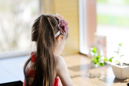 Little child girl sitting at a table facing away from the camera photo