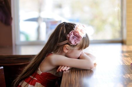Thoughtful brunette child girl sitting at a table in restaurant photo