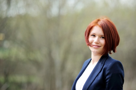 red haired girl: Portrait of beautiful woman with red hair posing outdoors