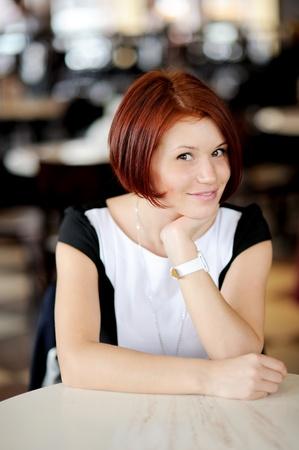 a bob: Retrato de mujer hermosa con el pelo rojo, sentado en una mesa Foto de archivo