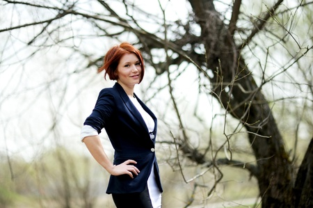 short haired: Beautiful woman with red hair in business suit posing outdoors