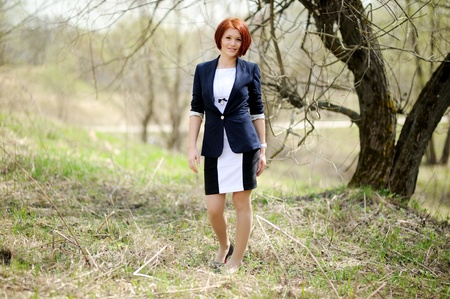 Beautiful woman with red hair in business suit posing outdoors photo
