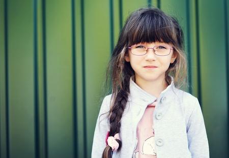 Portrait of brunette toddler girl in glasses against green wall