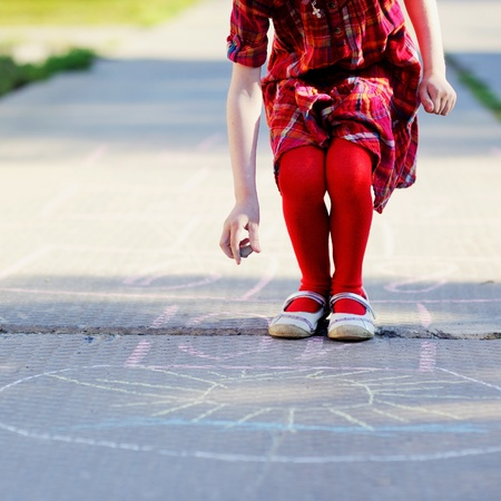 Child girl in red dress playing hopscotch on asphalt