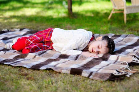 Little preschool girl sleeping on red plaid on grass in a garden photo