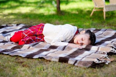 Little preschool girl sleeping on red plaid on grass in a garden Stock Photo - 13560888