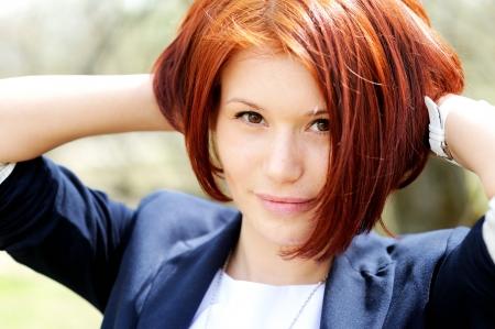 короткие волосы: Крупным планом портрет красивой женщины с рыжими волосами позирует на открытом воздухе