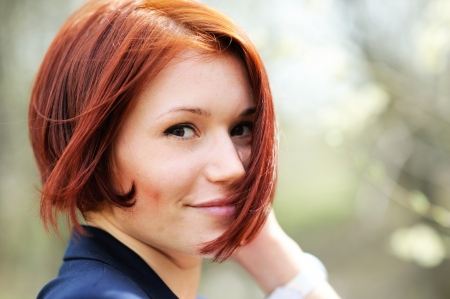 short: Close-up portrait of beautiful woman with red hair posing outdoors
