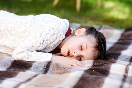 Portrait of preschool girl sleeping on plaid in a garden photo