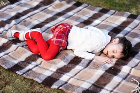 pantyhose: Little preschool girl sleeping on red plaid on grass in a garden Stock Photo