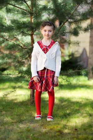 Pretty kid girl posing outdoors in a garden photo