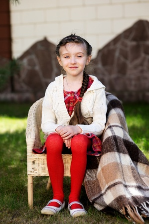 Pretty preschool girl sitting in a chair outdoors photo