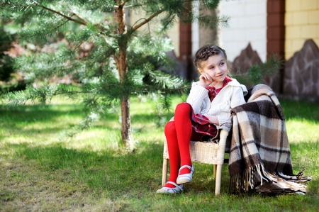 Pretty preschool girl sitting in a chair outdoors photo