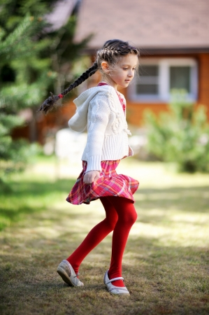 Pretty kid girl dancing outdoors in a garden photo