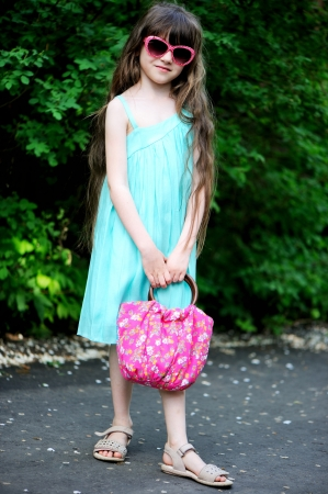 sandalias: Retrato de cuerpo entero de la niña pequeña en gafas de sol de color rosa posando al aire libre en un día soleado