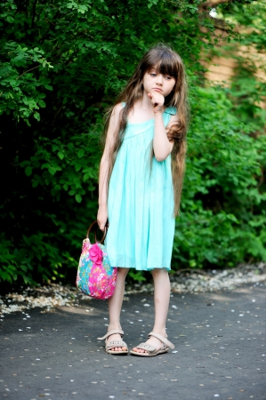 sandal tree: Full length portrait of little child girl in turquoise dress posing outdoors on a sunny day Stock Photo
