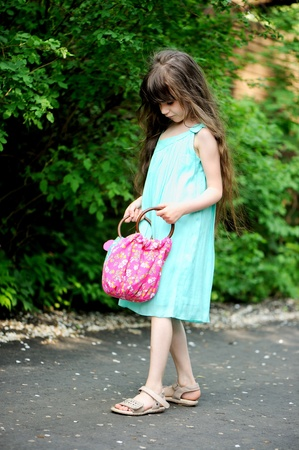 Full length portrait of little child girl checking the contents of her bag while walking along the street Stock Photo - 13854345