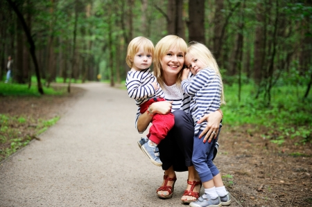 single parents: Outdoor portrait of a young mother posing with her children in the forest