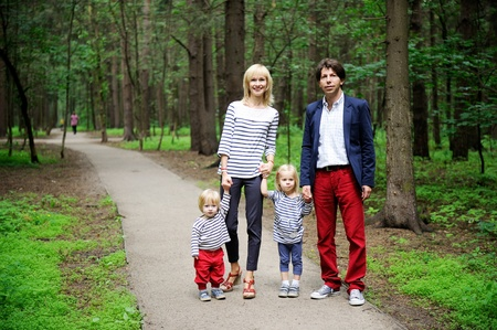 Outdoor portrait of a amazing family walking together in forest park photo
