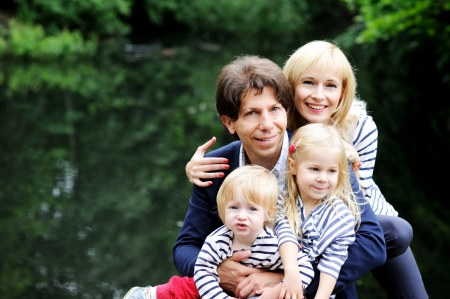 Outdoor portrait of a amazing family walking together in forest park Stock Photo - 14302287