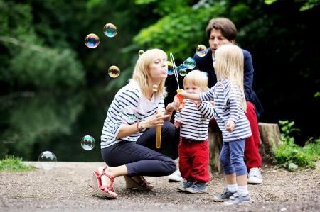 parentalidade: Fam�lia feliz com as duas crian�as se divertindo enquanto soprando bolhas juntos no parque