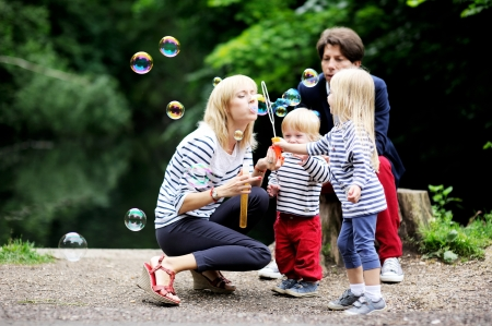woman blowing: Happy family with two children having fun while blowing bubbles together in the park Stock Photo