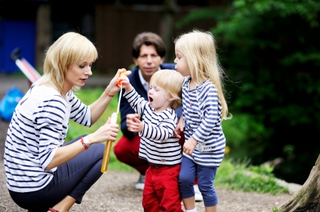 Happy family with two children having fun while blowing bubbles together in the park photo