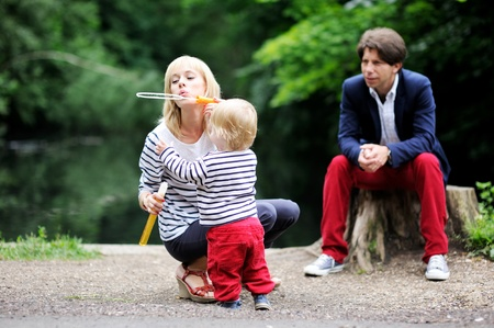 Happy family with a child boy having fun while blowing bubbles together in the park photo