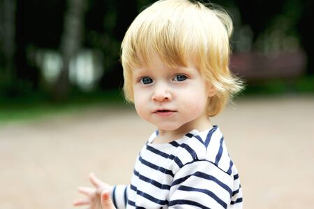 blond boy: Close-up portrait of cute baby boy posing outdoor Stock Photo