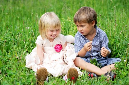 Portrait of cute child boy and girl sitting on green grass photo