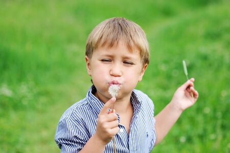 Portrait of toddler boy blowing dandelion outdoors photo