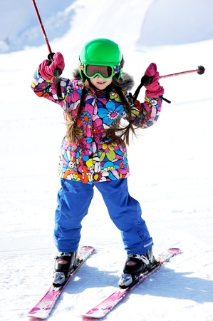 Portrait of little girl skier in sports suit finishing the ride Stock Photo - 14302198