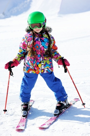 downhill skiing: Portrait of little girl skier in sports suit finishing the ride Stock Photo