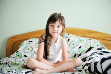 innocent girl: Portrait of little girl sitting in bed in early morning Stock Photo