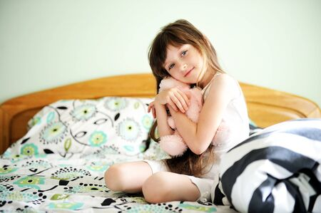 innocent girl: Portrait of little girl sitting in bed with a toy in early morning