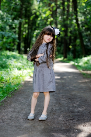Little girl in grey dress posing in summer forest photo