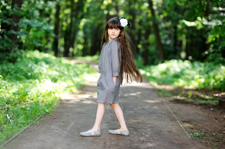 hair bow: Little girl in grey dress posing in summer forest
