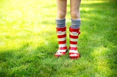 botas de lluvia: Imagen de las piernas del ni�o en un c�sped verde que lleva botas de lluvia de color rojo a rayas